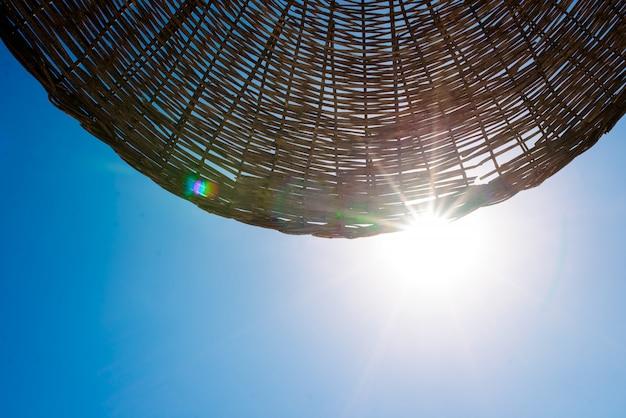 太陽は浜辺の傘を通して輝いています。 Premium写真