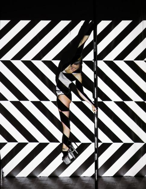 Красивая женщина танцует возле шеста на полосатой стене Premium Фотографии