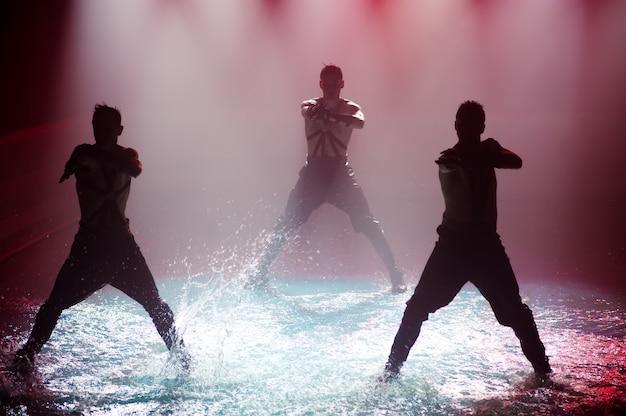クラブライトに対するダンスグループの水上パフォーマンス。 Premium写真