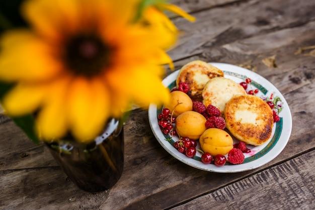 花と木のテーブルに果実を焼くの静物画。 Premium写真