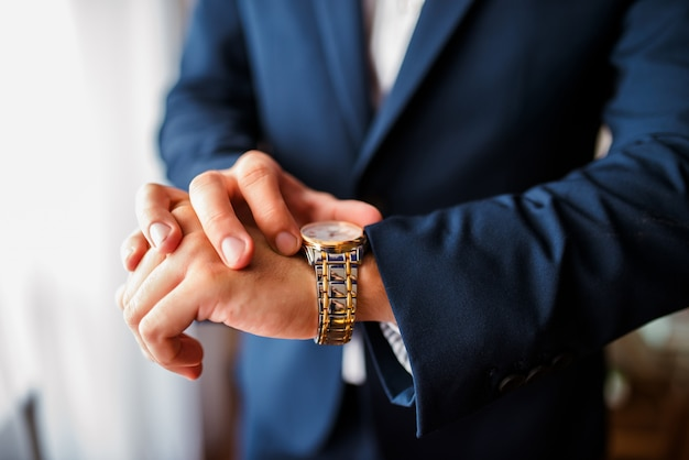 青いスーツを着た男は時計の時間を見ています。 Premium写真