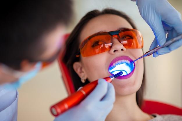 光の治療は歯科で美少女をシールします。 Premium写真