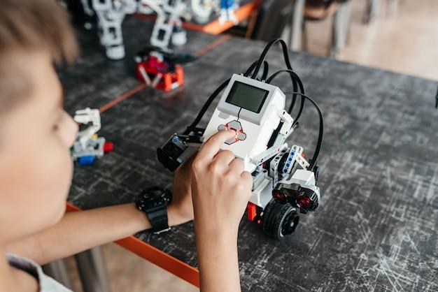 Подросток играет с роботом за столом. Premium Фотографии