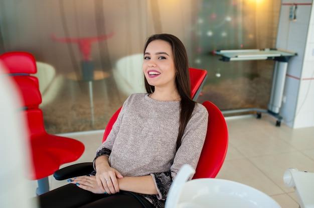 Красивая девушка улыбается в стоматологическом кресле. Premium Фотографии