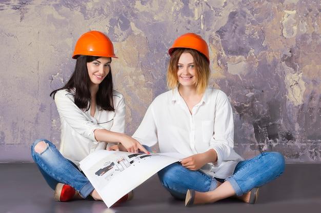Девушка женщины счастливых смешных милых архитекторов женская в оранжевых шлемах здания предохранения от конструкции сидя на поле с чертежами и проектами архитектуры. Premium Фотографии