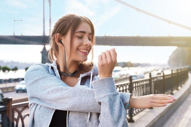 Молодая женщина улыбается делает утреннюю растяжку на улице города. красивая девушка в беспроводных наушниках готовится к бегу, бег трусцой. концепция спортивного и здорового образа жизни. Premium Фотографии