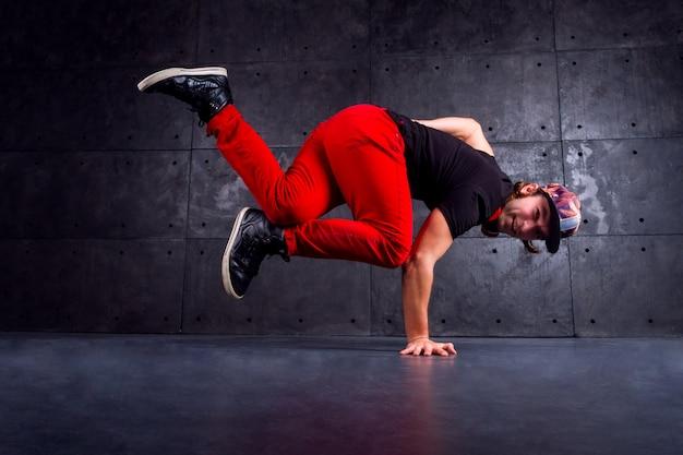 スタイリッシュなモダンな赤いズボンを着て踊るブレイクダンサー Premium写真