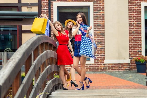 ショッピングの後通りを歩いて買い物袋とカラフルなドレスとハイヒールでかなり幸せな明るい女性女性女の子 Premium写真