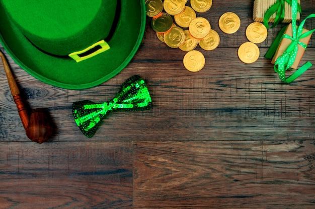 聖パトリックの日。レプラコーン、緑の蝶ネクタイ、喫煙パイプ、木製の背景の金貨の緑の帽子 Premium写真