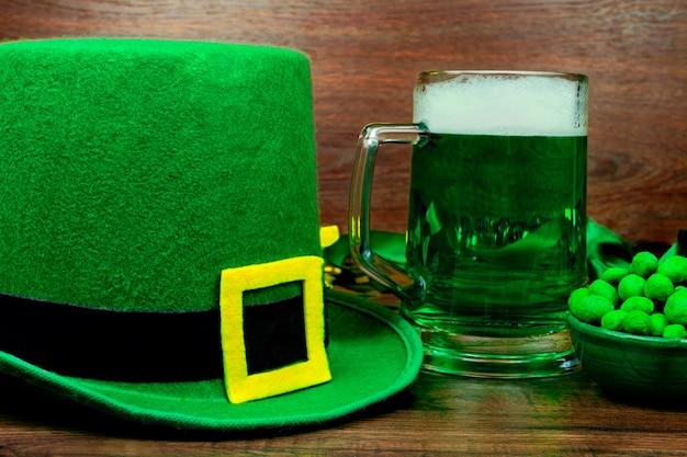 聖パトリックの日。ビールの緑のガラスのパイント、緑のスナッククッキーお菓子、木製のテーブルにレプラコーンの緑の帽子 Premium写真
