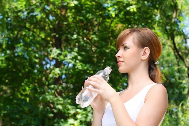 女性は森で水を飲む Premium写真