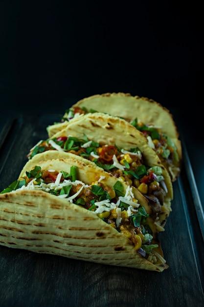 木の板に肉、チーズ、コーン、玉ねぎ、豚肉のハーブとメキシコのタコス Premium写真