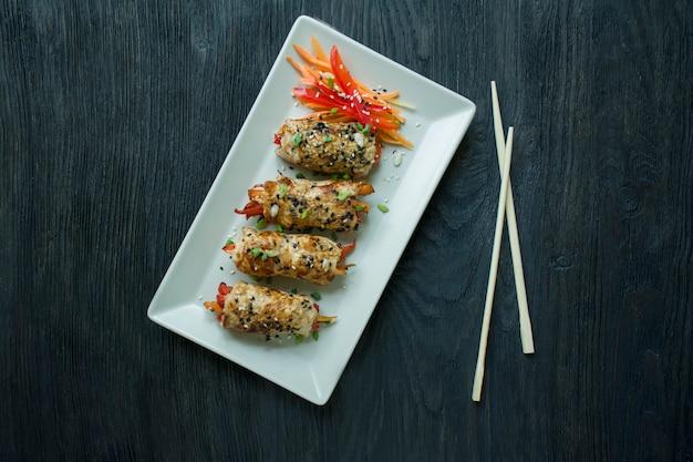 自家製鶏の胸肉は、野菜、にんじんスライス、ピーマン、薄い長方形のプレートに巻きます。 Premium写真