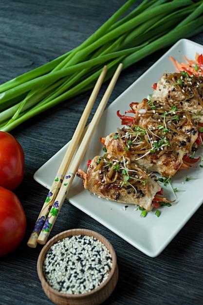 新鮮な鶏の胸肉と野菜、ニンジンスライス、ピーマン、暗いまな板の上でロールします。 Premium写真