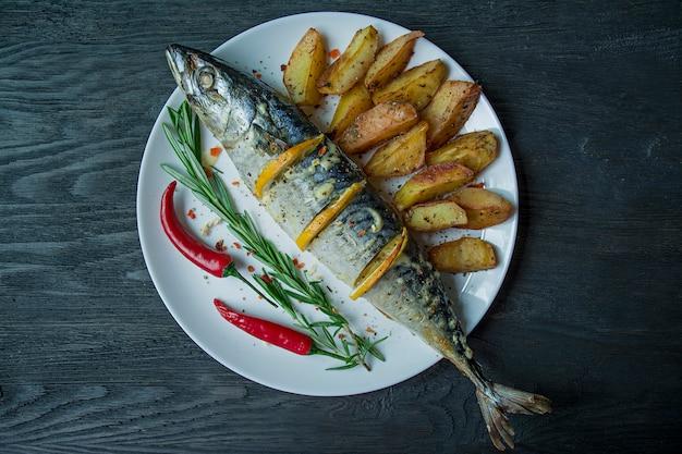 白い皿にレモンとベイクドポテトの焼きサバ。 Premium写真