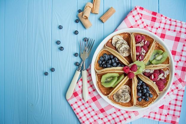 青い木製のテーブルに新鮮なベリーと古典的なアメリカのパンケーキ。フルーツのパンケーキ。 Premium写真