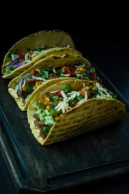 木の板に肉、チーズ、トウモロコシ、玉ねぎ、ポークハーブとメキシコのタコスの写真。ケチャップソースと唐辛子。 Premium写真
