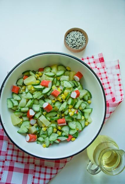 Салат с кукурузой, крабовыми палочками, огурцами в белой миске на белом фоне Premium Фотографии