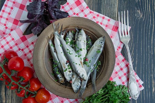 バルト海のニシンのシーフード。ニシン魚をボウルにスパイスとハーブで塩漬け。 Premium写真