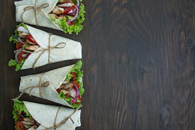 メキシコ料理。チキンと野菜のクローズアップで包まれたブリトー Premium写真