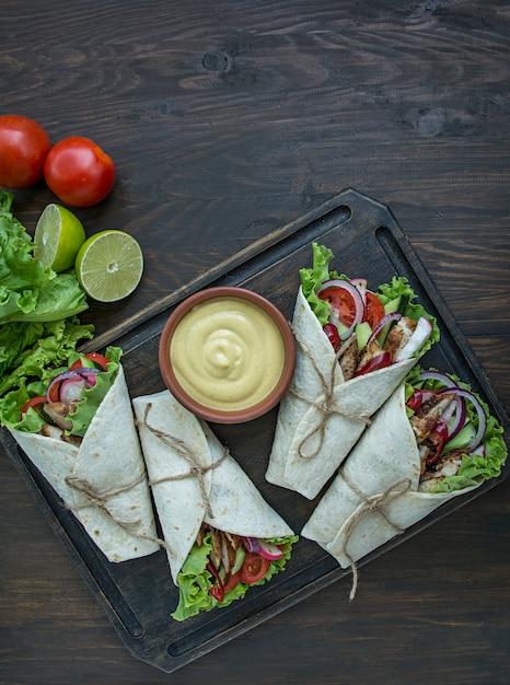 木製のテーブルにチキンと野菜のクローズアップで包まれたブリトー。 Premium写真