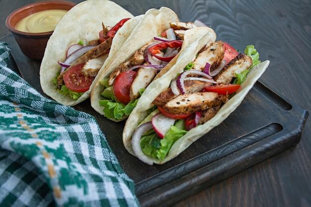 メキシコ料理。木製の背景にチキンと野菜のクローズアップで包まれたブリトー。テキスト用のスペース。 Premium写真
