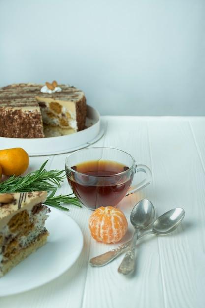 Чай в стеклянной чашке на светлой деревянной предпосылке. черный чай с розмарином и мандаринами. пространство для текста. Premium Фотографии