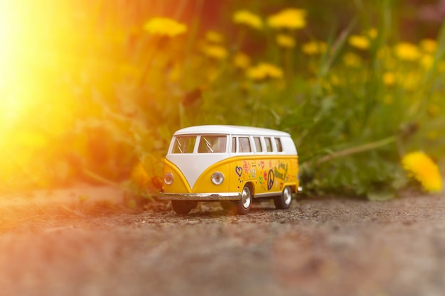 日光の下で咲くタンポポのレトロなバスのおもちゃ Premium写真