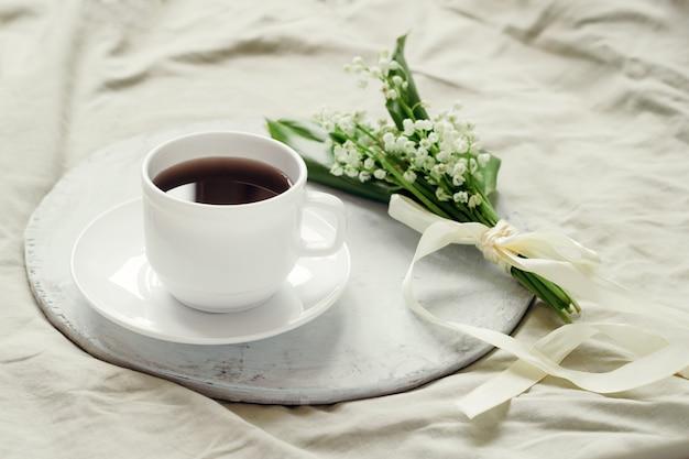 シルクリボンと淹れたてのコーヒーで飾られた谷の新鮮なユリの繊細な花束 Premium写真