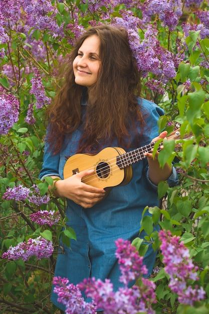 ウクレレを演奏デニムドレスを着た巻き毛を持つ美しい女の子 Premium写真