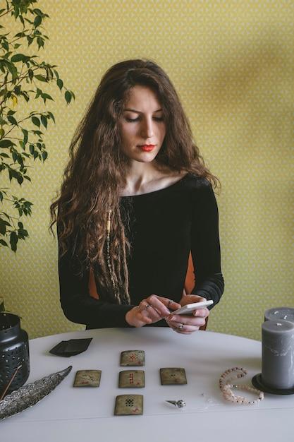 ルーン文字のカードで黒いコーデュロイドレスの美しい若い女性を推測しています Premium写真