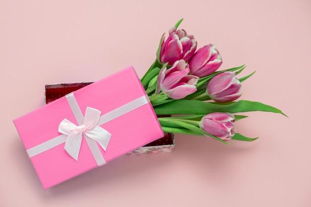 Вид сверху розовых тюльпанов в коробке с розовой атласной лентой, бантом на пастельно-розовом Premium Фотографии