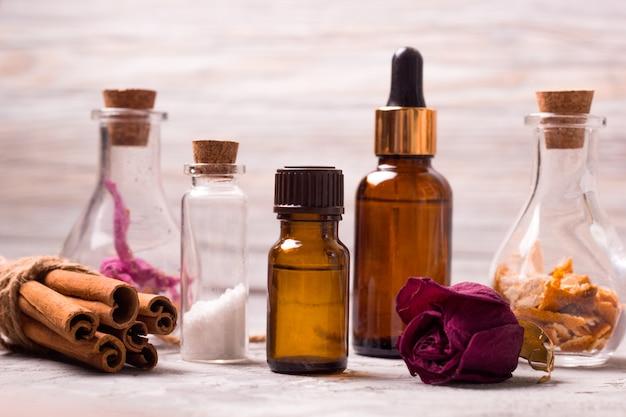 Спа набор бутылок: сухие лепестки роз, апельсиновая цедра, ароматические масла, морская соль, корица Premium Фотографии