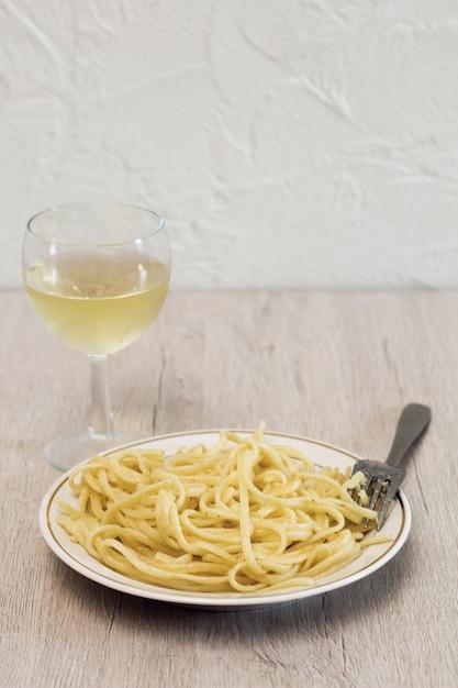 パスタと白ワイングラス、木製のテーブル Premium写真