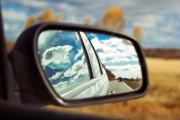 Голубое небо с пушистыми облаками и отражение дороги автомобильное зеркало на фоне осеннего поля Premium Фотографии