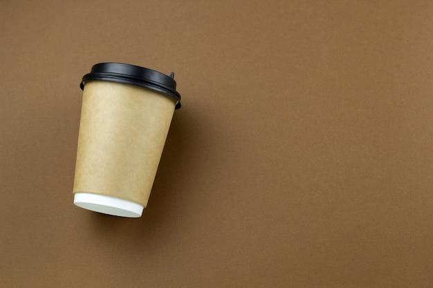 茶色の背景に使い捨ての紙コップ Premium写真