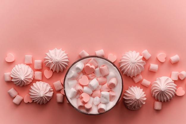 Вид сверху горячий напиток со взбитыми сливками, зефиром и тонированными шоколадными конфетами в форме сердца Premium Фотографии