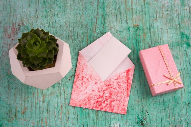 ピンクのギフト、多肉植物のポットボックスと白紙の封筒封筒ぼろぼろの木製の背景 Premium写真