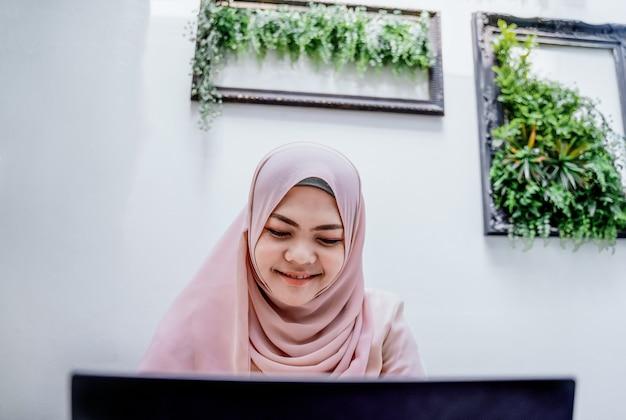 自信を持って若いイスラム教徒の女性がノートパソコンを入力します。白い部屋に座っている笑顔のアラブ女性。 Premium写真