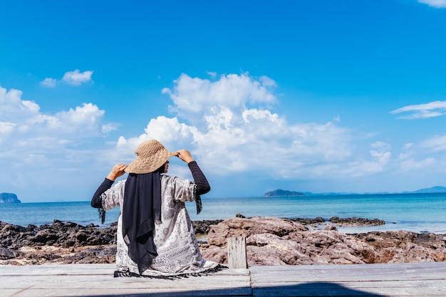 木製の歩道から見ている若いイスラム教徒アジア女性の背面図です。未来と研究の概念海の上に立っている女性。旅行の概念 Premium写真
