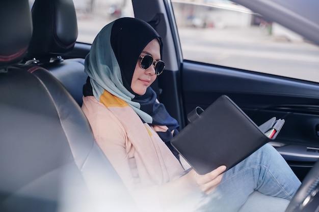 車の後部座席で読書若いイスラム教徒のビジネス女性の肖像画を間近します。 Premium写真