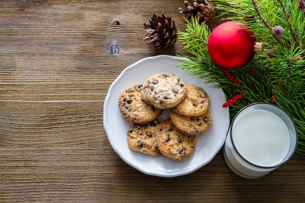 クッキーとミルクのサンタクロースウッドの背景に Premium写真