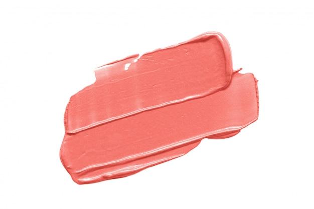 白で隔離されるトレンディなサンゴ色の口紅汚れ Premium写真