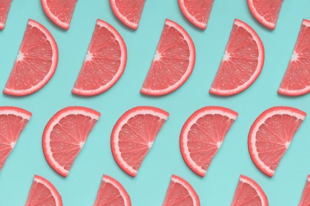 パステルブルーの背景にピンクグレープフルーツ等尺性パターン Premium写真