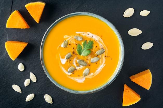 ボウルにバタースカッシュのスープ。バタースカッシュのスライスとスレートボード上の種。健康的なベジタリアン料理。ハロウィーン、感謝祭のディナー。スペースをコピーします。 Premium写真