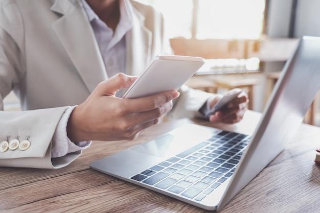 オンライン決済、コンピューターのラップトップを使用してオンラインショッピングでスマートフォンモバイルとクレジットカードを保持している若い男の手。 Premium写真