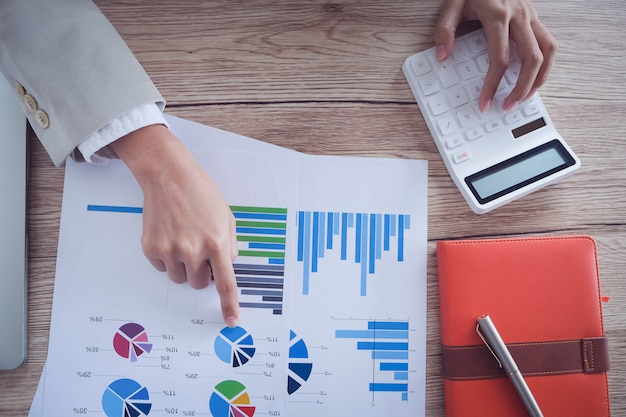 ビジネス会計の概念、ビジネス男ペンポインティンググラフと電卓を使用してオフィスで予算とローンの紙を計算します。 Premium写真