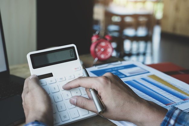電卓を使用してペンを保持し、ラップトップコンピューターを使用して年次バランスシートを確認するビジネスの男性 Premium写真