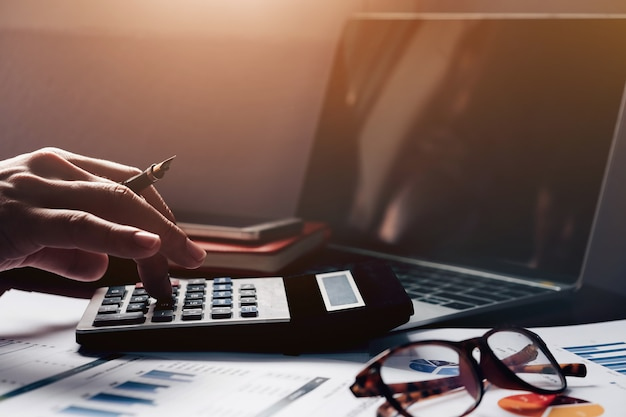 Бухгалтерский учет, бизнесмен используя калькулятор с компьтер-книжкой компьютера, бюджет и бумагу займа в офисе. Premium Фотографии
