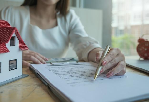 Агенты по недвижимости обсуждают кредиты и процентные ставки на покупку домов для клиентов, которые приходят на контакт. понятия договора и соглашения. Premium Фотографии